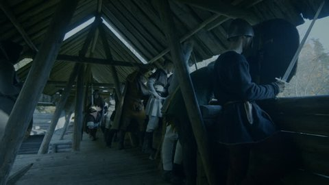 Large-Scale Medieval Battle Reenactment. Guards on the Wall of the Wooden Fortress Get Ready to Repulse Attack. They Fight with Axes, Swords, Spears. Shot on RED EPIC-W 8K Helium Cinema Camera.