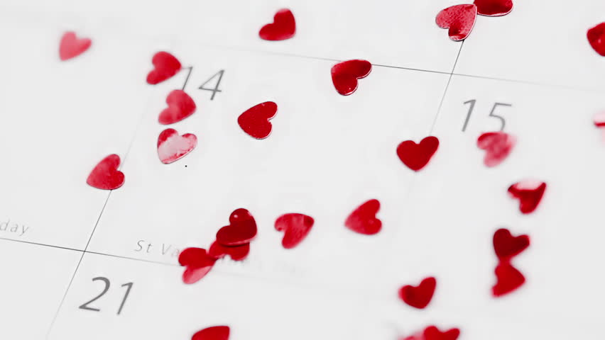 Pink heart confetti falling on calendar showing Valentines day