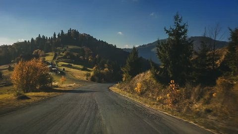 Low Aerial Footage View: Fast car ride along the rural road, farming land and houses, autumn mountains with forests, meadows and hills. Carpathian Mountains, Ukraine, Europe. Nature landscape. Full HD