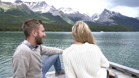Cheerful couple sitting on wooden pier above mountain lake in Canada making a heart shape finger frame on beautiful scenery. People love travel concept Shot at Maligne lake, Canada