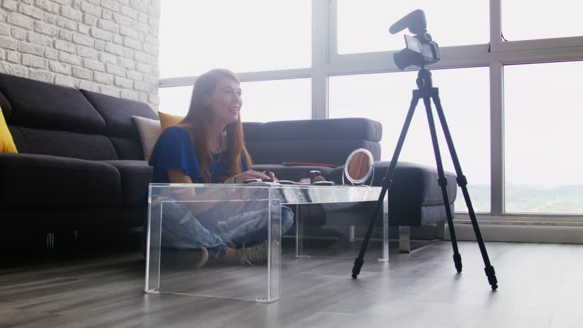 Happy girl at home speaking about make up in front of camera. People and technology, young woman working as video blogger. Web influencer recording for Instagram, social media, Facebook, internet   Shutterstock HD Video #33562510