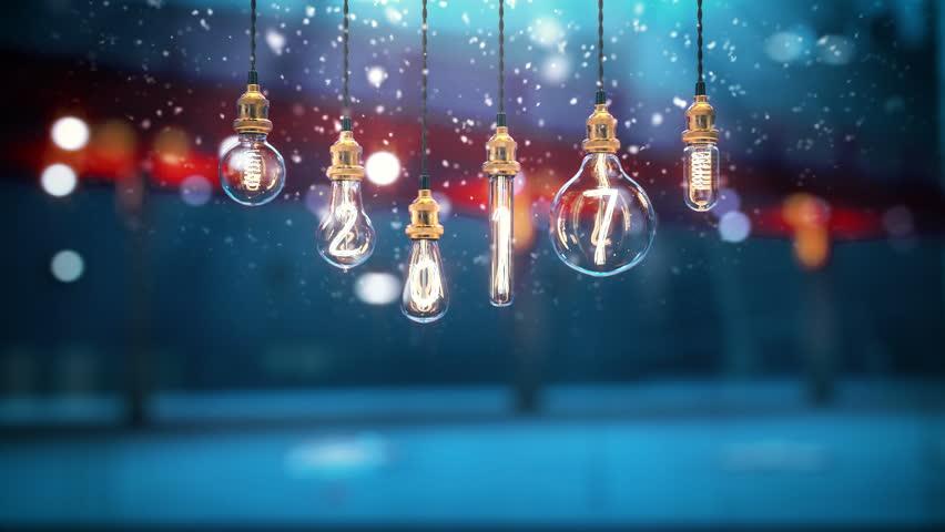 turning on 2018 edison light bulb. Christmas light, snow in God rays. New year 2018.