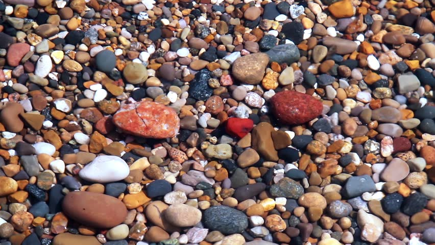 Seamless loop features waves over colorful beach pebbles in shallow water. Shot on the Indiana coast of Lake Michigan at 1920x1080p HD widescreen.