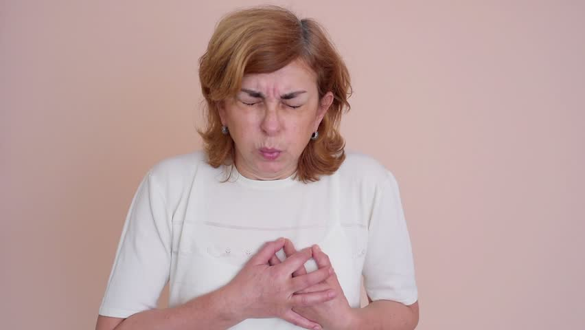 Woman with heart attack holding her chest
