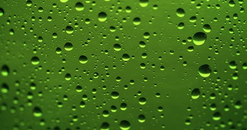 Drop of condensate drips on beer bottle glass 4k extreme close-up video. Water drops falling down on green background