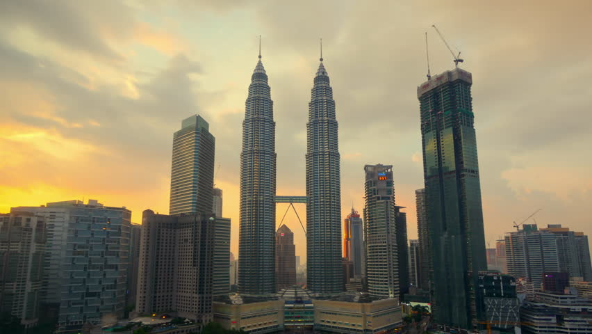 KUALA LUMPUR - CIRCA MAY 2017: Beautiful cloudscape timelapse with zooming in camera motion of the Petronas Twin Towers in sunset time on May 2017 at Kuala Lumpur City Center KLCC