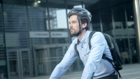 Close-up shot of a handsome commuter cycling to his office. Happy smartly dressed man riding a bike. Active and healthy way of traveling to job.