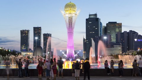 Bayterek Tower and fountain show day to night timelapse. People walking around. Skyscrapers on background. Bayterek is a monument and observation tower in Astana. Astana, Kazakhstan