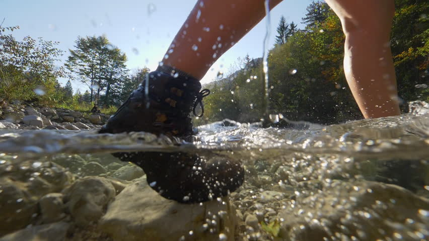 SLOW MOTION, HALF UNDERWATER Female hiker in mountaineering boots crossing river. Girl crossing river with brown leather boots. People trekking over rocky riverbed in mountain valley on sunny fall day