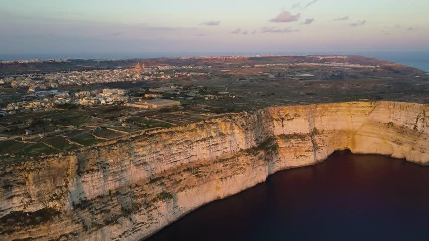 4k aerial drone footage - Famous Ta Cenc Cliffs of the island of Gozo, Malta at sunset.