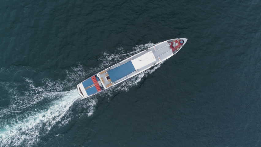 Small white cruise ship is sailing in sea. Drone is hovering. Aerial vertical top down view.