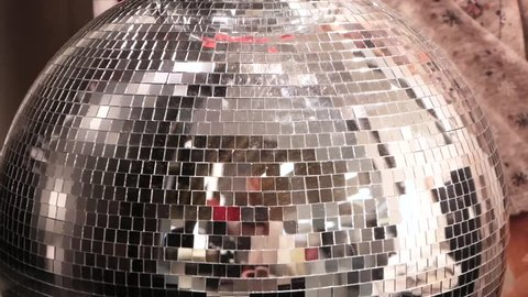 Shiny disco ball with silver reflection and rays, close-up