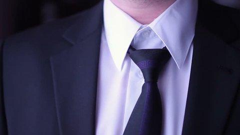 Businessmann corrects his necktie