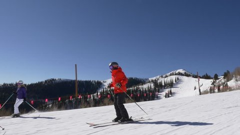 Cameraman skis alongside, tracking, with family on sunny, winter day at Park City, Utah.