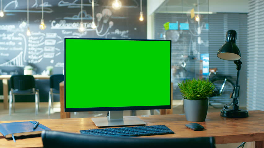 Personal Computer with Mock-up Green Screen Monitor Stands on the Office Desk. In the Background Man Works in the Creative Office at Daytime | Shutterstock HD Video #33748600