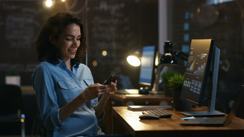 Beautiful Female Financier Uses Mobile Phone, Writing Messages, Emails while Smiling.In the Background Creative Office with Employees.  | Shutterstock HD Video #33749680