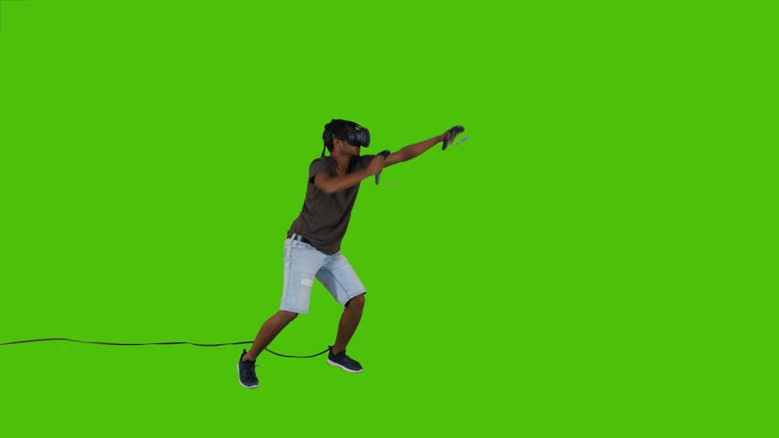 Enthusiastic First person shooting with guns in a VR video game by a young man over a green screen, casual look, long shot. #33776110