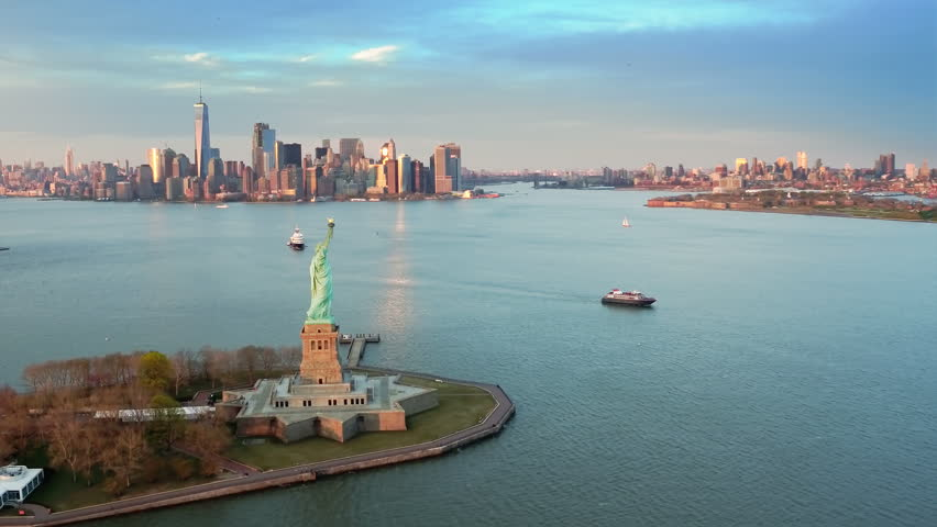 Aerial view of the Statue of Liberty at sunset. Manhattan and New Jersey skyline in the background. New York City, United States. Shot from a helicopter. #33800830