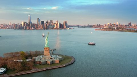Aerial view of the Statue of Liberty at sunset. Manhattan and New Jersey skyline in the background. New York City, United States. Shot from a helicopter.