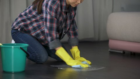 Lady trying to get rid of stains on floor with special remover, polishing