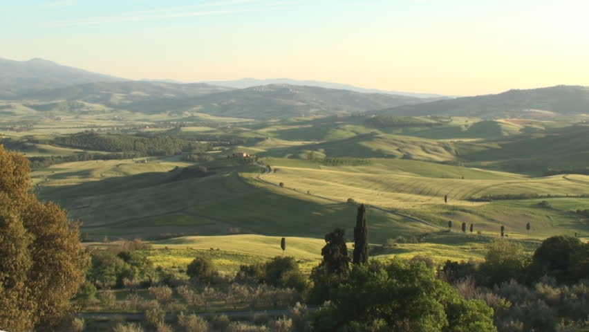 Pan of Val d'Orcia in the province of Siena in Tuscany, Italy at sunset
