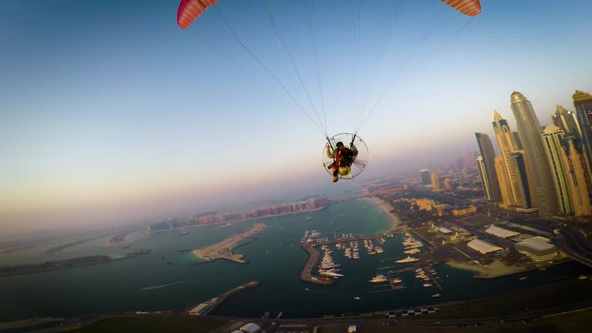 Paramotoring powered paragliding ppg flight high in beautiful evening sunset sky on calm blue Dubai beach ocean seascape