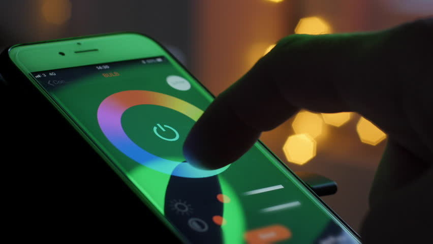 Smart home lighting technology, controlling color of a bulb and scheduling time with a smart phone. Remote controlling light with a phone app. 4k Video | Shutterstock HD Video #33848320