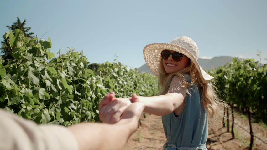 Beautiful woman holding hands with boyfriend leading through grape vines summer holiday travel wanderlust