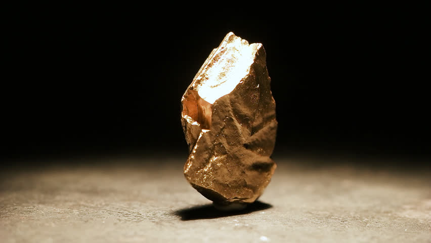 Closeup of a big gold nugget, slow motion footage