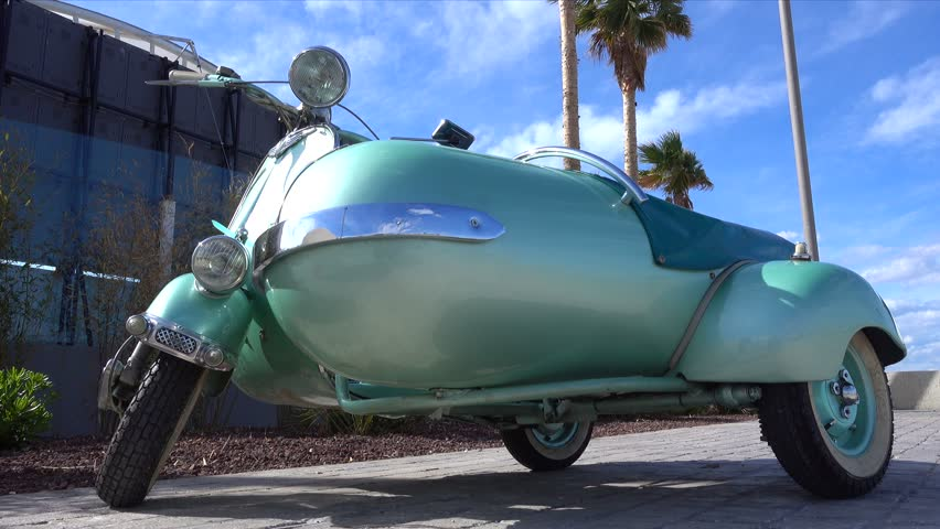 Turquoise Vespa Piaggio scooter with sidecar . The Vespa is a classic Italian scooter very famous in the world , cinematic 4k footage