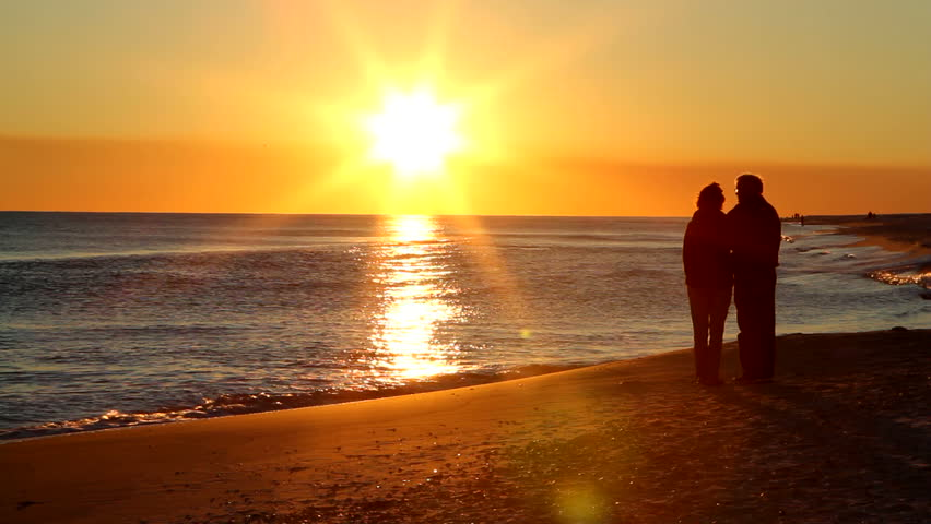 Retired married senior couple stand together on the seashore watching the sun go down on the ocean.