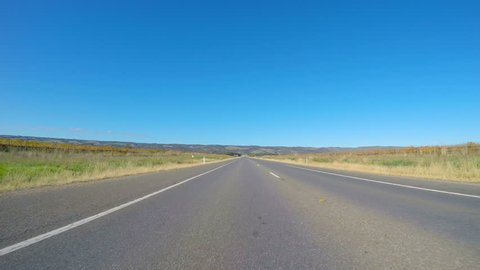 Vehicle POV, driving along wide, flat open highway through McLaren Vale South Australia.