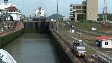PANAMA CANAL/PANAMA - 9TH APRIL 2011: Panama mule pulls ship into Miraflores lock Panama Canal. Container ship MSC Carmen is in the background