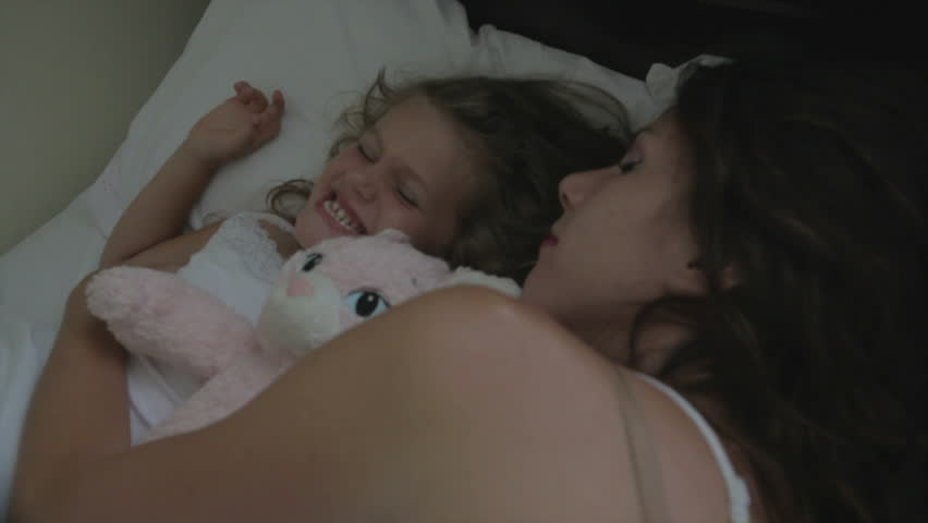 Mother sleeping with little girl