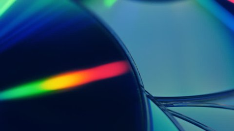 Many compact discs lying on top of each other rotate and shimmer in different colors. Macro. Closeup. Shallow depth of field