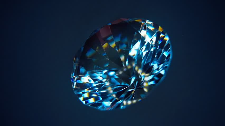 The diamond is rotation and shimmer all the colors of the rainbow when it hits the rays of light. Isolated on blue and black background. Macro. Closeup