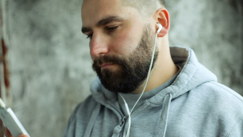 art, people, emotions, music, 4K and lifestyle concept - Model released man in studio puts ear phones rocks, electronic out to music. Young handsome bearded man listens music smartphone in earphones #33914890