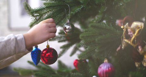 Hanging Christmas decoration on tree with Christmas lights. Decorating on Christmas tree with ball. 4K