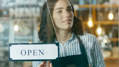 Beautiful Young Cafe Owner Turning Storefront Sign From Close to Open and Welcoming Customers into Stylish Coffee Shop. Big City with Traffic and People Visible in Window Reflection. 4K UHD.
