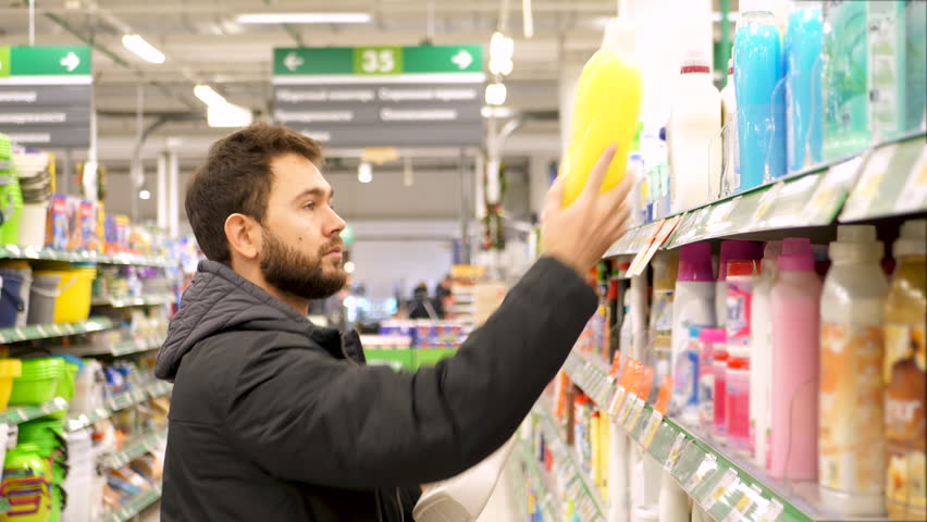 Young man chooses household chemicals in the supermarket. 4K UHD