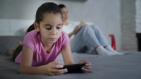 Dangers of Technology and Internet for Young People. Little Girl Spends Too Much time on Mobile Phone. Mother Reading Worries. Daughter Disconnected.