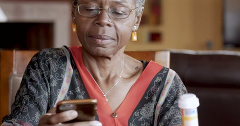 Attractive black senior woman over 50 refilling her prescription to a pharmacy or talking to her health care professional about her health care on a smart phone