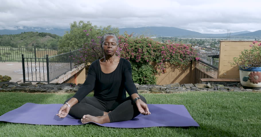 Healthy African American senior in 60s sitting cross legged meditating outside on a yoga mat - dolly shot