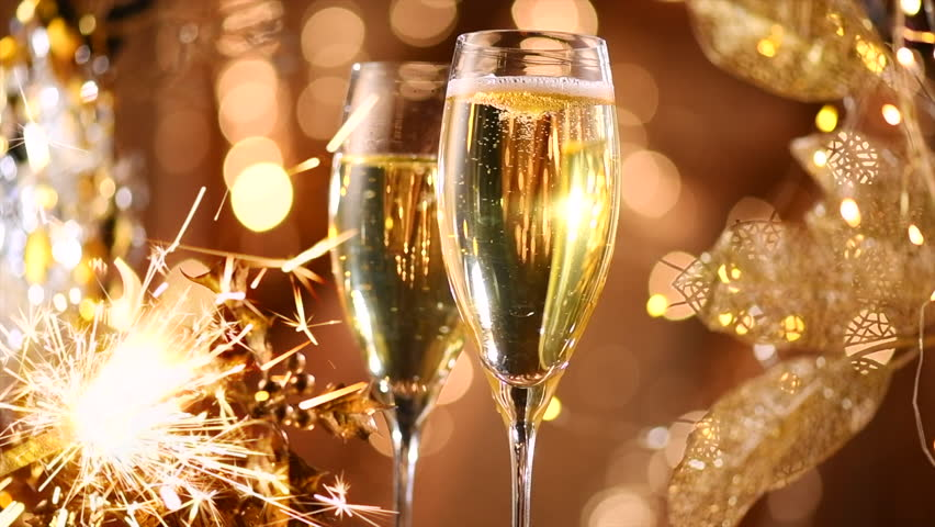 christmas and new year champagne over golden glow background winter holidays celebration two flutes with sparkler champagne over holiday bokeh blinking