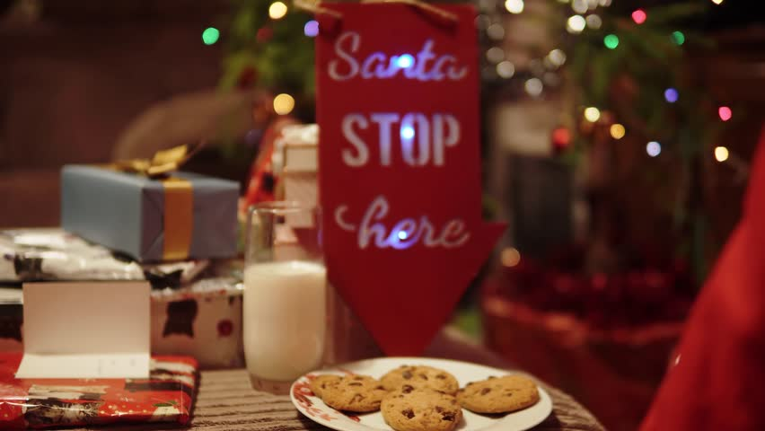 Santa Claus Visits Home Christmas Eve, Takes Cookies And Milk, Presents. A Variety Of Camera Angles Available. Father Christmas Joyful Scene.