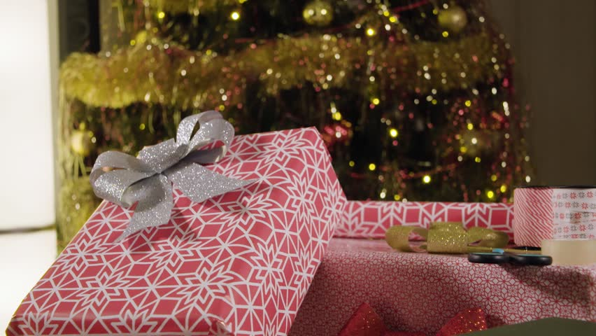 A Woman Puts A Bowknot On A Gift Box In A Christmas-decorated Living ...