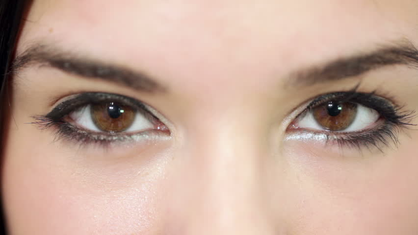 Young beautiful woman with striking brown eyes, make-up. Shallow depth of field. closeup.