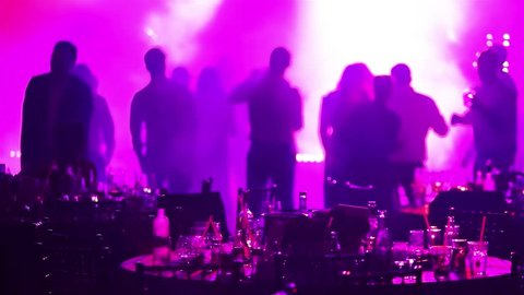 A party in a restaurant, silhouettes of people dancing in a disco, banquet tables in a restaurant, stage lights and music, people at a banquet in a restaurant, group of young people, unrecognizable
