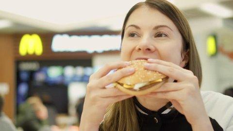 MOSCOW, RUSSIA - CIRCA November 2017: Hungry teen girl eating hamburger at McDonald's on food court. Woman biting cheeseburger at fast food restaurant