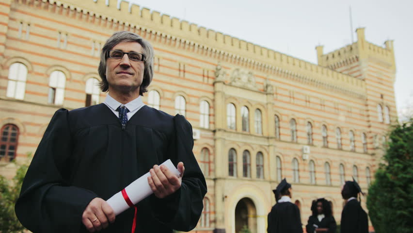 Portrait of the gray-haired male professor in glasses and black gown representing the University in front of it. Graduates on the background. Outdoor | Shutterstock HD Video #34025440